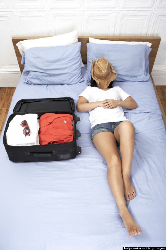 Woman lying on bed next to full suitcase, face obscured by sun hat