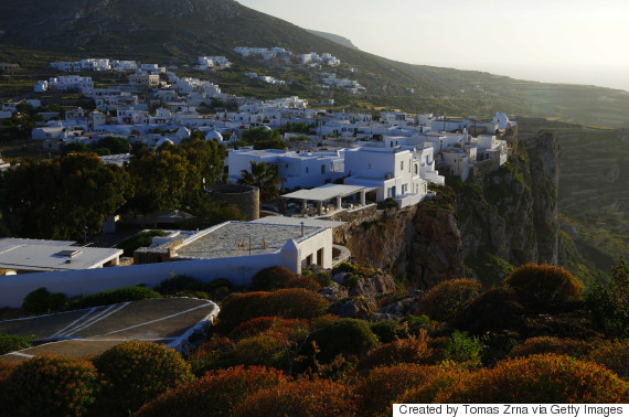 Evening gentle sunlight illuminates clifftop Chora settlement, Folegandros island, Cyclades, Greece